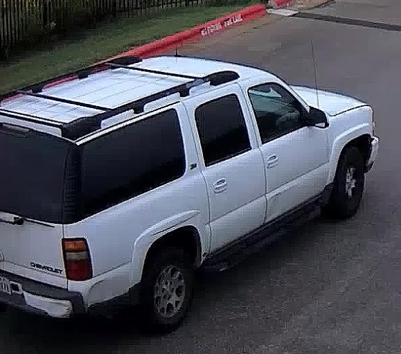 The vehicle is described as a white Chevrolet Suburban.  Possibly mid-2000's model year with a black roof rack with peeling paint and a dent on the front passenger side door and back right side of the bumper.