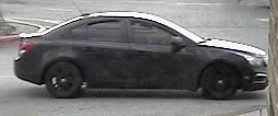 Suspect vehicle is a dark colored (possibly dark gray) Chevy Cruz with black rims.  The vehicle is missing the front license plate.